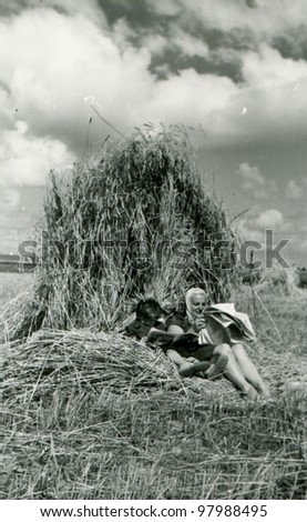 Vintage photo of mother and daughter reading newspapers under a sheaf (fifties) - stock photo