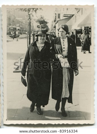 Vintage photo of  mother and daughter walking on the street (thirties) - stock photo