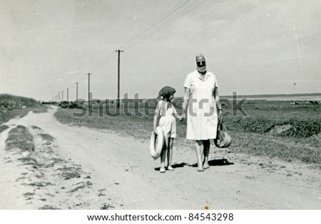 Vintage photo of mother and daughter walking together (fifties) - stock photo