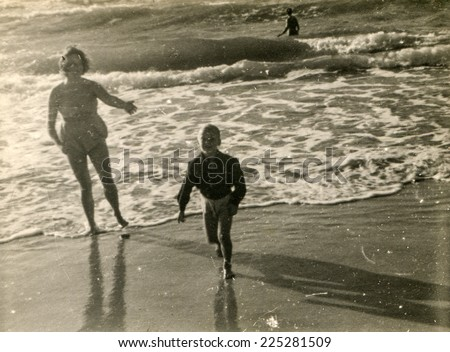 Vintage photo of mother and little son on beach, forties - stock photo