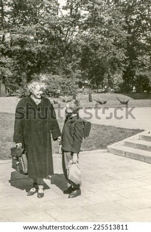 Vintage photo of mother and son with school backpack, early fifties - stock photo