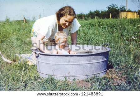 Vintage photo of mother bathing her baby daughter in a washtub (1982)