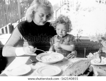 Vintage photo of mother feeding her daughter, fifties - stock photo