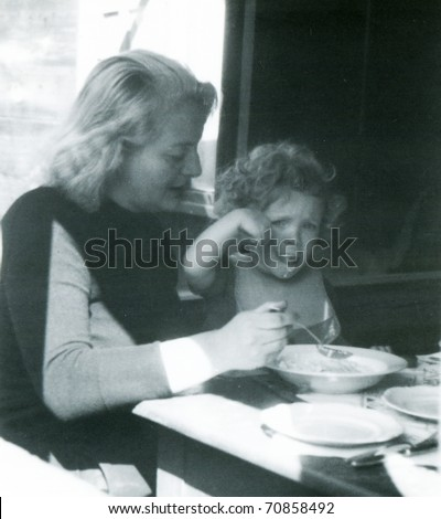 Vintage photo of mother feeding her daughter (fifties) - stock photo