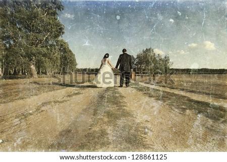 Vintage photo of newlywed couple walking away on dusty road - stock photo