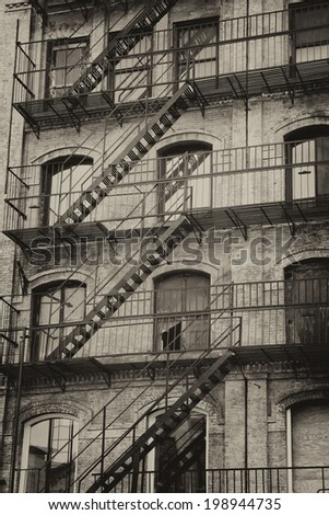 Vintage photo of old building with outdoor staircase (New York City, USA).Vertically. Processed as a vintage photo. - stock photo