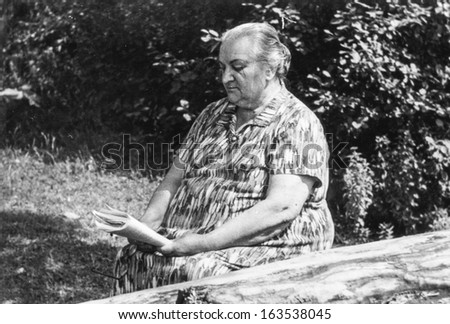Vintage photo of overweight elderly woman reading outdoor, fifties - stock photo