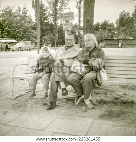 Vintage photo of parents sitting on bench with little daughter, fifties