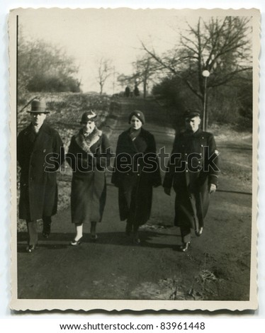 Vintage photo of  parents, son and daughter walking on the street (thirties) - stock photo