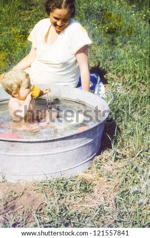Vintage photo of pregnant mother and daughter bathing in a washtub (1981) - stock photo