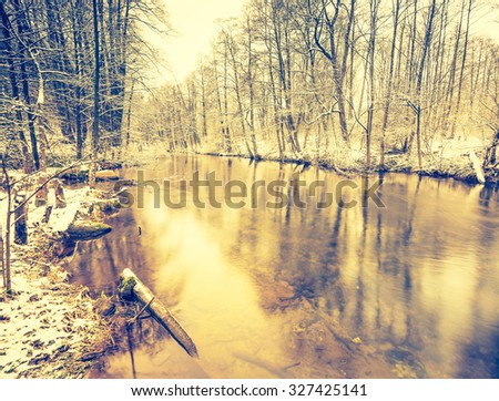 Vintage photo of river in forest at winter. Beautiful winter time photo with vintage mood effect. - stock photo