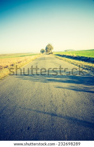 vintage photo of rural landscape with asphalt road
