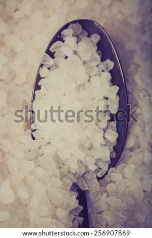Vintage photo of sea salt grains on a spoon - stock photo