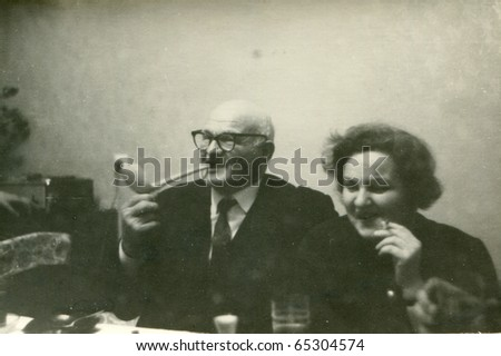 Vintage photo of senior father and adult daughter smoking