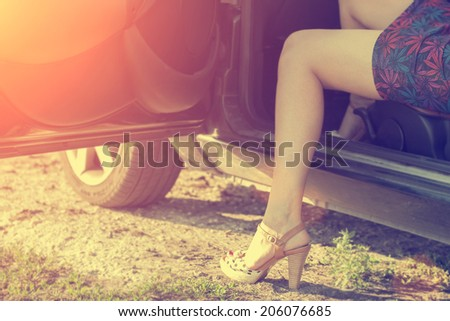 Vintage photo of sexy woman legs out of car - stock photo