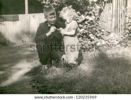 Vintage photo of siblings playing outdoor (fifties) - stock photo