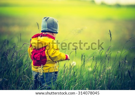 Vintage photo of small child playing on meadow. Beautiful landscape with small child - stock photo