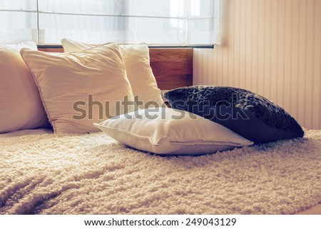 Vintage photo of stylish bedroom interior design with black and white pillows on bed. - stock photo