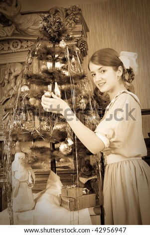 Vintage photo of Teen girl decorating Christmas tree at home
