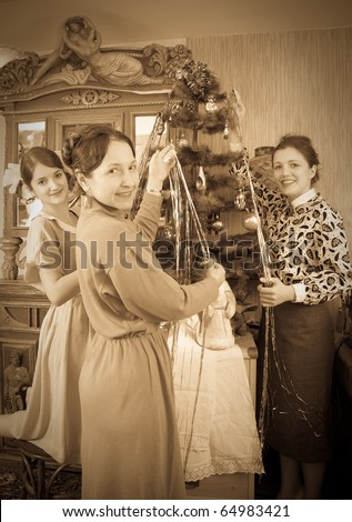 Vintage photo of  Teen girls with mother decorating Christmas tree at home