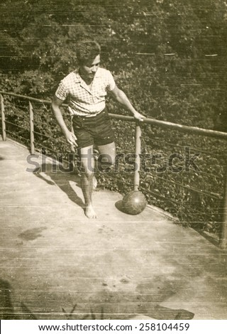 Vintage photo of teenager playing with a ball, 1960's - stock photo