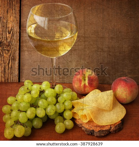 Vintage photo of the Mediterranean delicious snacks. Glass of white wine, grapes, cheese and peaches on the wooden background.Old paper textured background with still life of delicious food and drink  - stock photo
