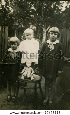Vintage photo of three sisters with a doll (thirties) - stock photo