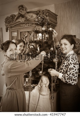 Vintage photo of  Three women decorating Christmas tree at home