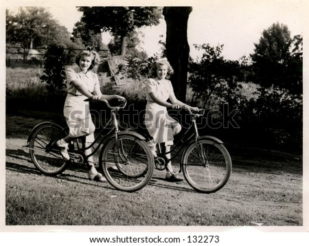 Vintage photo of twin sisters on bicycles. Circa 1930 - stock photo