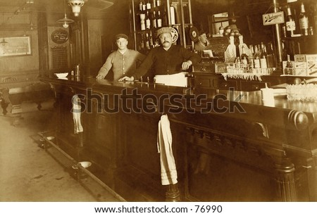 Vintage photo of two bartenders behind bar - stock photo