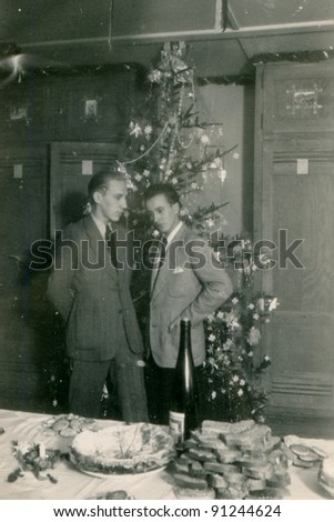 Vintage photo of two men at Christmas time (forties) - stock photo