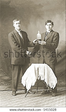 Vintage photo of Two Men Shaking Hands Holding Bottle Of Alcohol - stock photo