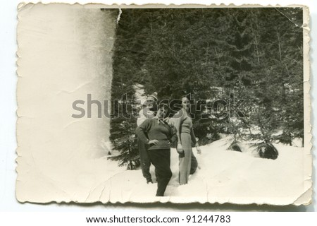 Vintage photo of two women and a man in winter (forties) - stock photo