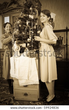 Vintage photo of  Two women decorating Christmas tree at home - stock photo