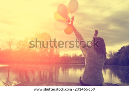 Vintage photo of woman having fun with balloons in sunset - stock photo