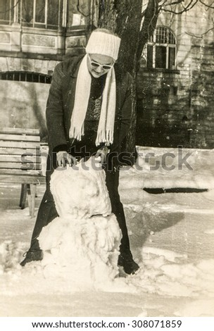 Vintage photo of woman making a snowman, 1950's - stock photo