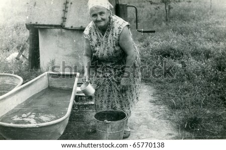 Vintage photo of woman making laundry outdoor - stock photo