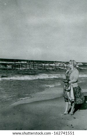 Vintage photo of woman on beach, fifties - stock photo