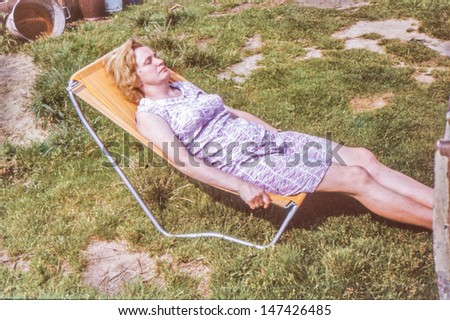 Vintage photo of woman relaxing on sunbed, seventies