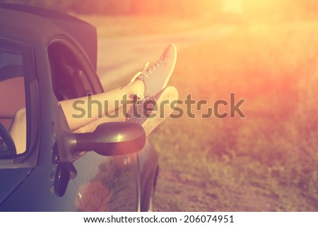Vintage photo of woman's legs in retro shoes out of car windows in summer sunset - stock photo