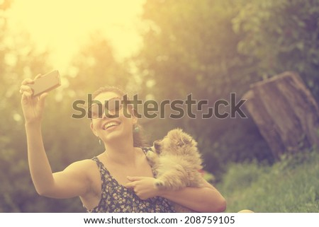 Vintage photo of woman taking a selfie with her dog - stock photo