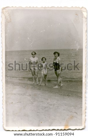 Vintage photo of women with girl on beach (fifties) - stock photo