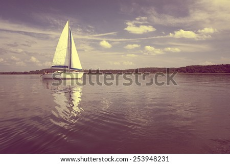Vintage photo of yacht sailing on the lake water, Mazury, Poland