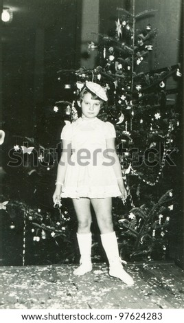 Vintage photo of young girl and Christmas tree (fifties) - stock photo