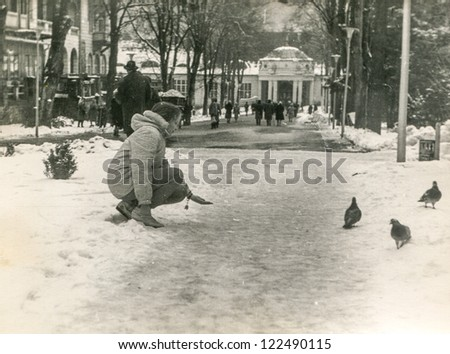 Vintage photo of young girl feeding pigeons in park (sixties) - stock photo