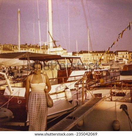Vintage photo of young girl in Saint Tropez port, seventies - stock photo