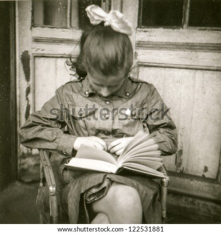 Vintage photo of young girl in scout uniform reading a book, early sixties - stock photo
