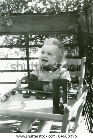 Vintage photo of young girl playing on balcony (fifties) - stock photo