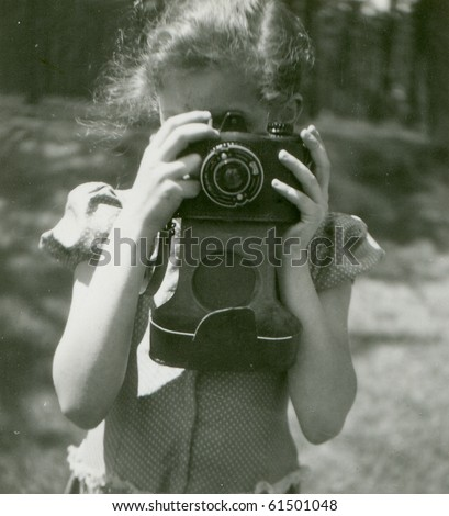 Vintage photo of young girl with camera (fifties) - stock photo