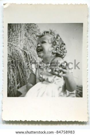 Vintage photo of young girl with doll (fifties) - stock photo